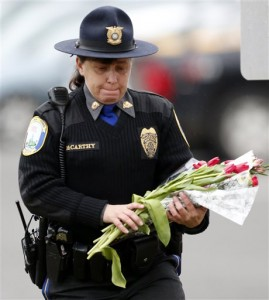 Newtown Police Officer Maryhelen McCarthy places flowers at a makeshift memorial outside St. Rose of Lima Roman Catholic Church, Sunday, Dec. 16, 2012, in Newtown, Conn. On Friday, a gunman allegedly killed his mother at their home and then opened fire inside the Sandy Hook Elementary School, killing 26 people. (AP Photo/Julio Cortez)