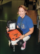Ellen Barkin holds the AED that saved the life of a senior basketball player, May 29, 2007 Garrett Richter