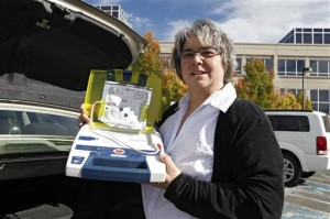 """In this Tuesday, Oct. 23, 2012 photo, Mary Tappe holds up the defibrillator that she keeps in the trunk of her automobile during a work break at the Western Union headquarters in Englewood, Colo. Tappe owes her life to bystanders' willingness to offer help. In 2004, she collapsed at her office in Iowa. A co-worker called 911; another quickly began CPR and someone else used the office's automated heart defibrillator. An ambulance took Tappe to the hospital, where doctors said her heart had stopped. They never determined why but implanted an internal defibrillator. Tappe, 51, who now lives in Englewood, Colo., said raising awareness about the importance of CPR is """"incredibly important because that's the first step"""" to helping people survive. (AP Photo/Ed Andrieski)"""