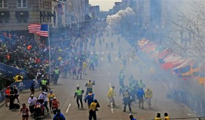 People react as an explosion goes off near the finish line of the 2013 Boston Marathon in Boston, Monday, April 15, 2013. Two explosions went off at the Boston Marathon finish line on Monday, sending authorities out on the course to carry off the injured while the stragglers were rerouted away from the smoking site of the blasts. (AP Photo/The Boston Globe, David L Ryan)