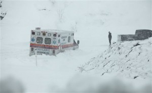 An ambulance is stuck in over a foot of snow off of Highway 33 West, near Belington, W.Va. on Tuesday, Oct. 30, 2012, in Belington, W.Va. Superstorm Sandy buried parts of West Virginia under more than a foot of snow on Tuesday, cutting power to at least 264,000 customers and closing dozens of roads. At least one death was reported. The storm not only hit higher elevations hard as predicted, communities in lower elevations got much more than the dusting of snow forecasters had first thought from a dangerous system that also brought significant rainfall, high wind gusts and small-stream flooding. (AP Photo/Robert Ray)