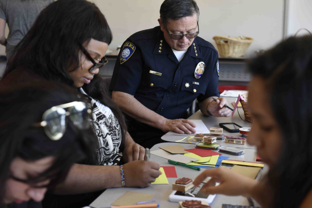 SMC student and Guardian Scholar Saprina Howard (left) and SMC Police Chief Johnnie Adams write notes for children entering or transitioning within the foster care system during a donation drive for Hope in a Suitcase held last month.