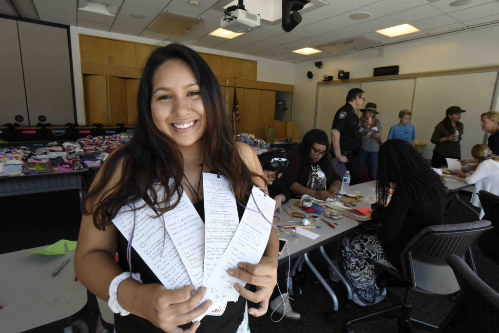 SMC student and Guardian Scholar Isabel Castillo holds up notes she wrote for children entering or transitioning within the foster care system during a donation drive for Hope in a Suitcase held last month.