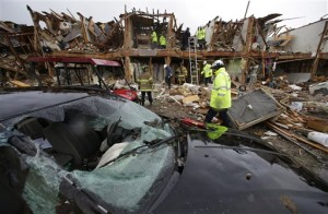 A smashed car sits in front of an apartment complex destroyed by an explosion at a fertilizer plant in West, Texas, as firefighters conduct a search and rescue Thursday, April 18, 2013. A massive explosion at the West Fertilizer Co. Wednesday night killed as many as 15 people and injured more than 160, officials said overnight. (AP Photo/LM Otero)