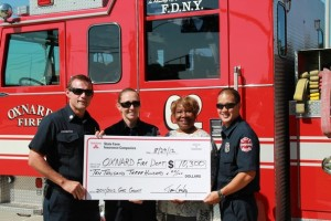 Oxnard Fire Department personnel, joined by City Councilmember Irene Pinkard, hoist an oversized check from State Farm signifying a grant that will help firefighters learn Spanish on iPads.